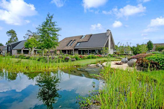 Moderne gevelboerderij met landelijke tuin en zwemvijver.