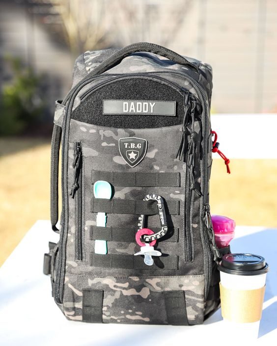 Tactical Baby Gear Military Diaper Bag. Best diaper bag gear for new Dads. Black camo pattern diaper bag to pack all of the essentials for a day out of Dad and baby time. Great for Army, Navy, Marine, coast guard, police, and first responders.