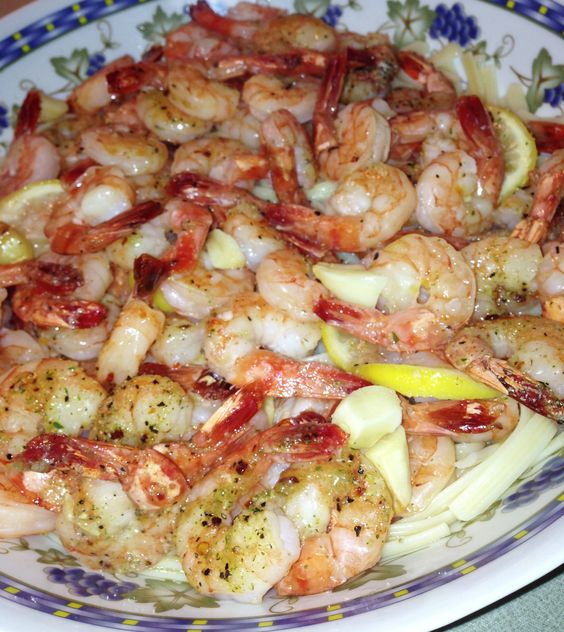 """Easy Italian Shrimp Scampi //  INGREDIENTS:  1-2lb uncooked, not frozen, peeled shrimps / / 1.5-2 pouches """"Good Seasons Italian Salad Dressing + Recipe Mix"""" / 1 box pasta (fettuccine, etc.) / 1-2 lemons (sliced) / Parmesan cheese / Garlic  // INSTRUCTIONS: 1. Preheat oven to 350 2. Cover entire bottom of flat cookie sheet w/ sliced lemons & little butter/oil 3. Put raw shrimps on lemons 4. Cover w/ seasoning & halved cloves of garlic 5. Bake for 20-25 mins 6. Serve on top of pasta w/parmesan"""