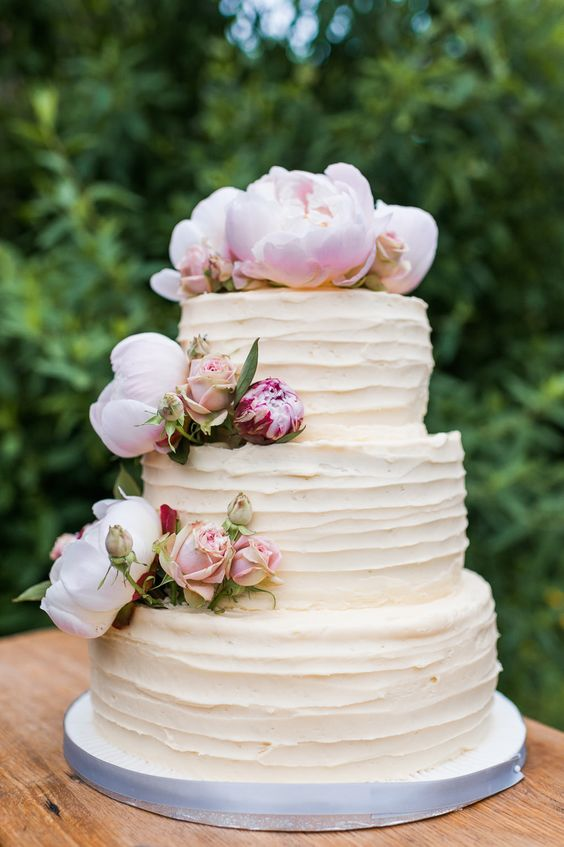 Home made three tiered wedding cake consisting of a bottom layer of carrot cake, a middle layer of red velvet cake and a top layer of chocolate cake, all covered with buttercream icing and decorated with pink peonies -  Image by  Ann-Kathrin Koch Photography - A wedding at Barnsley House with the bride in Suzanne Neville. A peony bouquet and white and blush colour theme. Mercury votive table decorations and white pom poms. Photography by Ann-Kathrin Koch.