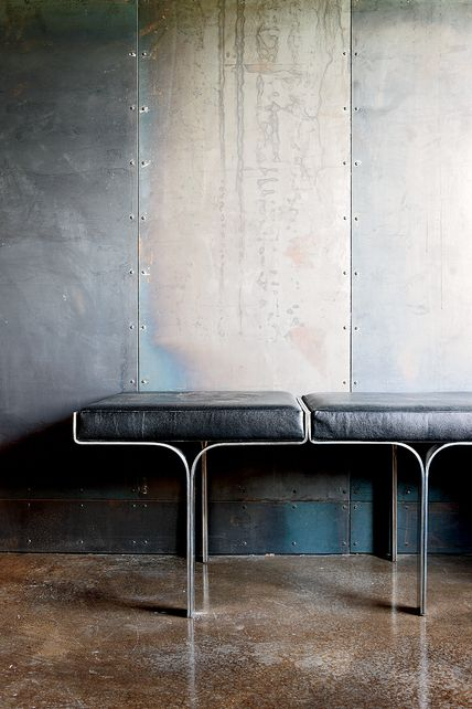 Galvanized-steel walls + concrete floors + aluminum/leather bench