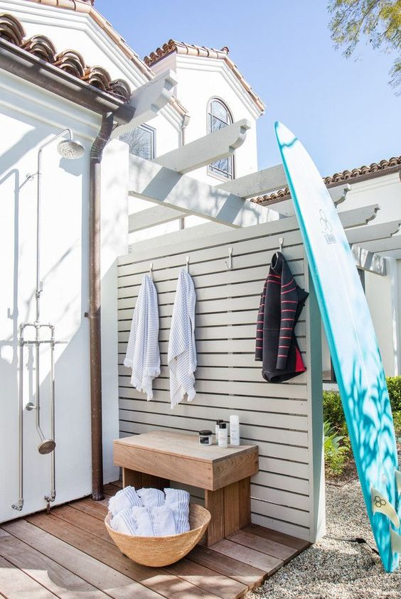 outdoor shower with surfboard and seating