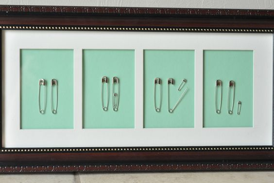 Simple wall hanging for baby's nursery--also makes a great baby shower gift! Easy to make, inexpensive family of safety pins.