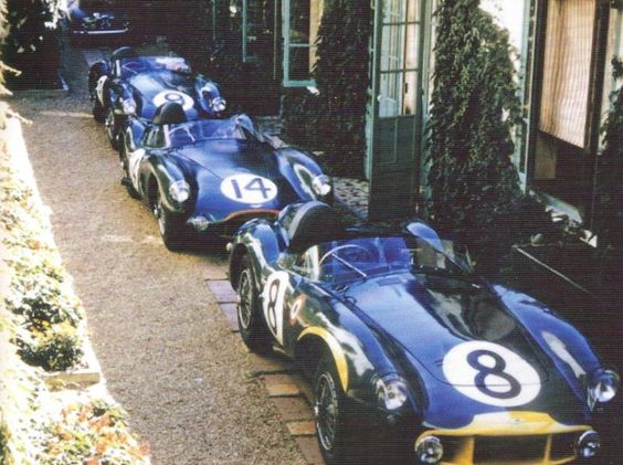 """1956: Aston Martins are parked behind the """"Hotel de France in La Chartre sur le Loir, headquarters of the team for the duration of their stay in France."""