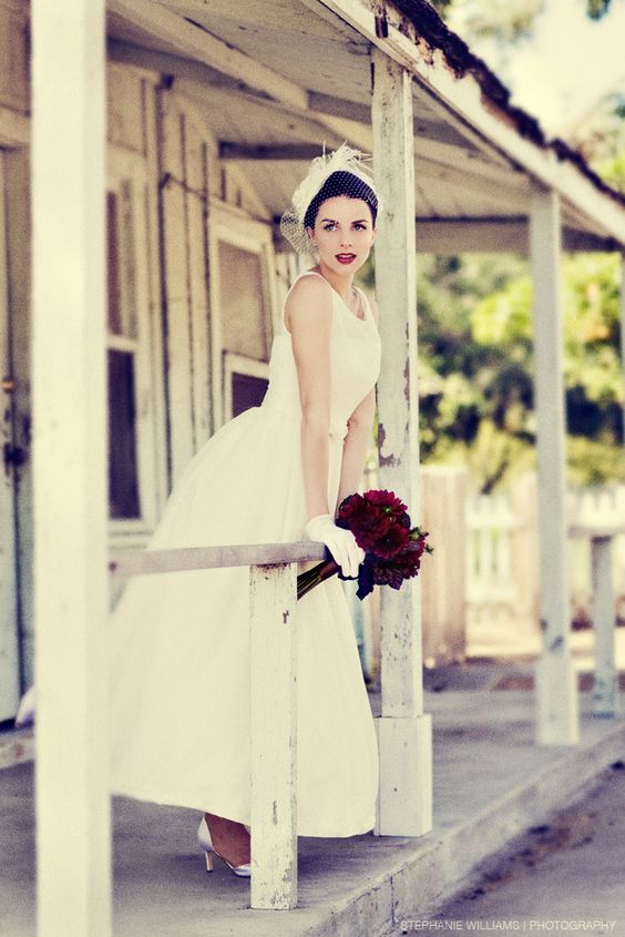 Vintage wedding hat with feathers, gorgeous urban location, retro wedding dress, dark red wedding bouquet