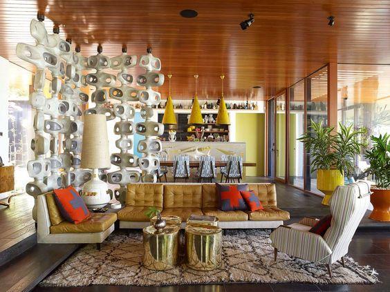 L'appartamento di Jonathan Adler & Simon Doonan a Shelter Island (Hamptons). Il sofà, i tavolini in ottone e il tramezzo in cemento bucato sono stati realizzati su ordinazione. I lampadari sono stati scovati a Parigi