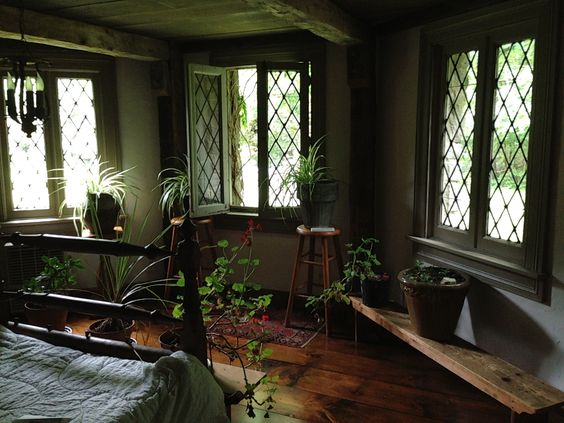 """Everyone's favorite bedroom is what we're calling the """"Hobbit Room."""" This bottom floor bedroom opens to the shade garden in the back and has a door leading under the breakfast room deck/trellis. It's quaint with stone walls, heavy beams and leaded glass windows. This room was an addition to the house so the outside stone wall became an interior one."""