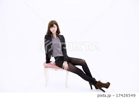 白い背景の前で椅子に横向きで座りながら両足を投げ出してポーズをとる微笑む若いスーツ姿の女性