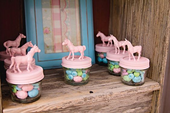 """""""I purchased mini plastic horses and hot glued them to tops of mason jars and then spray painted them pink,"""" Miranda says. """"Each container had a little bit of sweet for each child to go home with.""""  Source: Whimsically Detailed"""