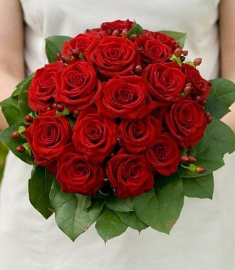 A fabulous classic bouquet with a distinctive collar of glossy green foliage, sprigs of hypericum berries and deep red roses make a bouquet that would be perfect for a winter or Christmas wedding