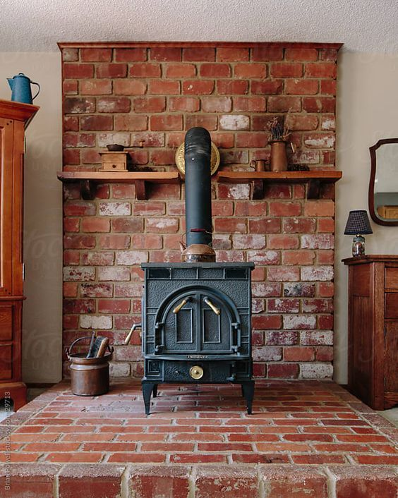 An Old Cast Iron Stove On A Brick Hearth Surrounded By Antique