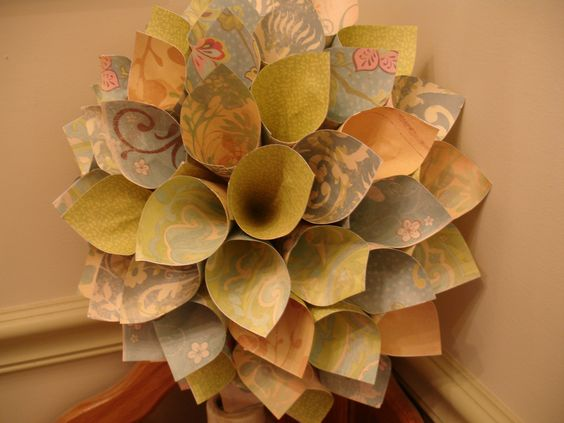This paper wreath is in shades of blue and green and resembles a dahlia.