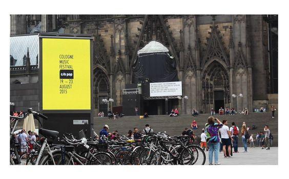 Screenanzeige vorm Kölner Hauptbahnhof für c/o pop festival 2015