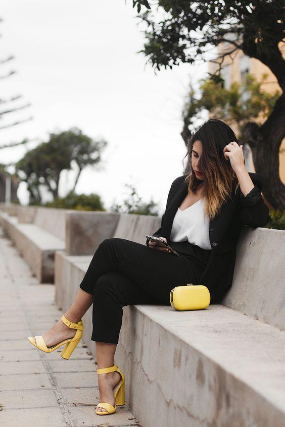 Mujer vestida de traje negro, blusa blanca sencilla y zapatos y bolso en amarillo