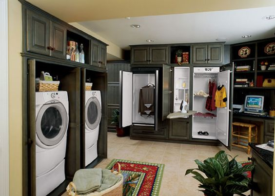 This dream laundry room features cabinets that hold all appliances, hanging items, ironing board, etc. that will neatly close up when chores are completed. Totally cool. Neat little built in desk space too.