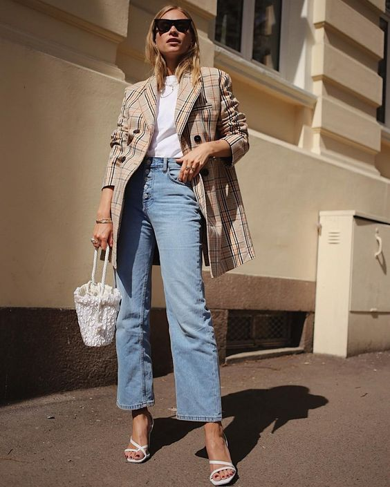 Vintage items that are back in style and worth the splurge. Seen here: Street style shot of girl wearing square toe strappy sandals, jeans, jeans, basket bag, white tee and oversized blazer.