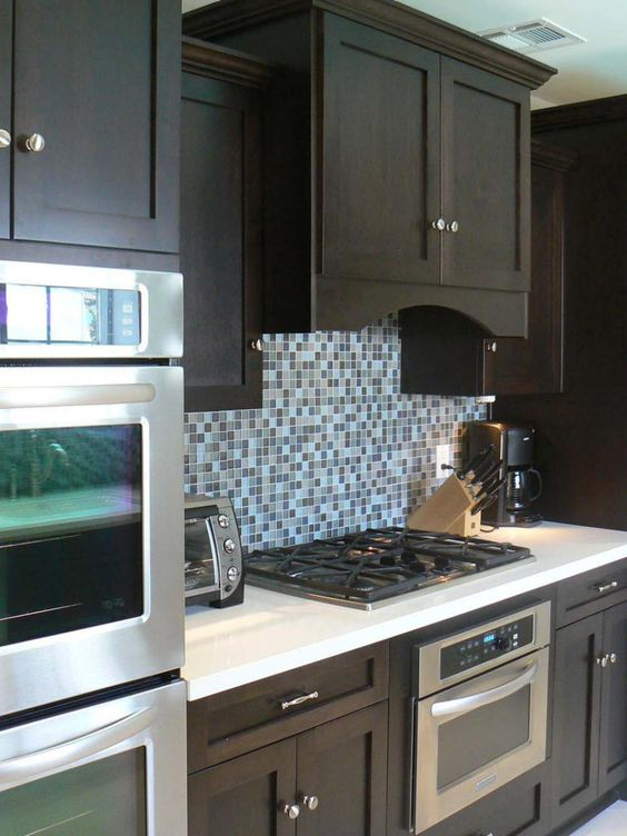 A blue and brown mosaic tile backsplash serves as the for Blue and brown kitchen
