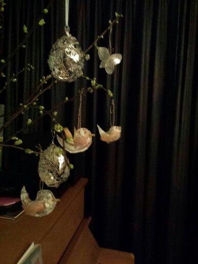 Metalen bloemetjes ei en stoffen vogeltjes op de achtergrond een vlinder van judaspenning.