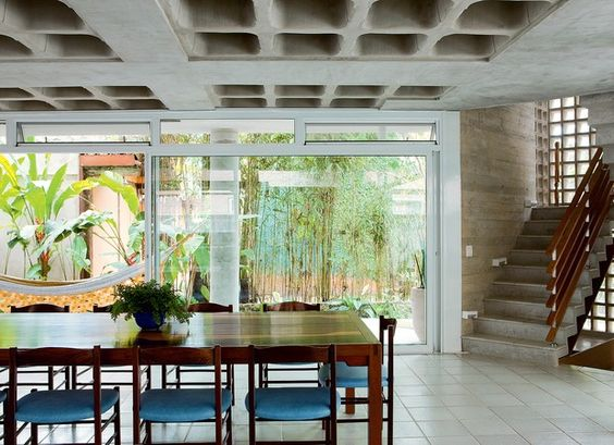 SALA DE JANTAR O ambiente é integrado ao jardim do fundo pelos painéis de vidro em caixilho de alumínio, da Jmar. No alto, a janela basculante garante a ventilação cruzada. À dir., a escada fica entre pilares retangulares e recebe luz natural de elementos (Foto: Edu Castello)