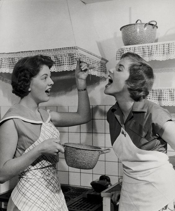 Huishouden, koken. Huisvrouwen met schorten proeven eten uit gewolkte emaille pan, in keuken met boerenbonten valletjes met kant langs schouw en planken. Nederland, 1950-1960.