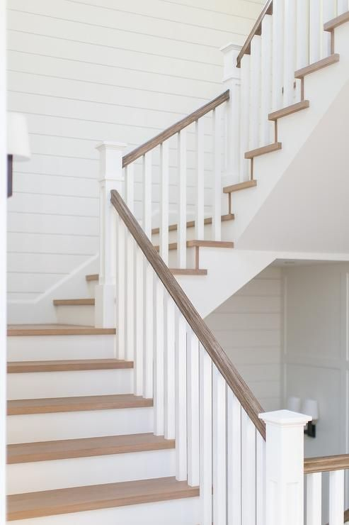 A Gray Wash Wood Rail Accents A White Staircase Fitted With White Spindles And Gray Wash Wood Treads A Staircase Handrail Wood Staircase Interior Stair Railing