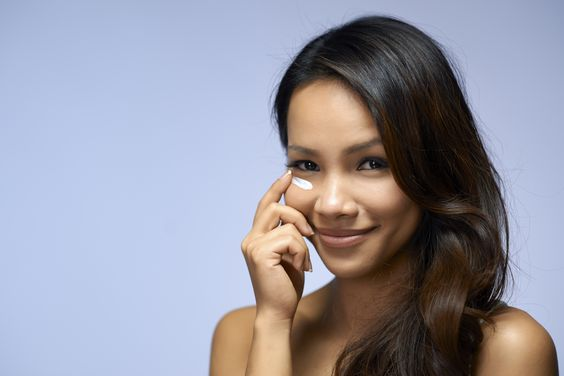 Asian girl using beauty cream and cosmetics