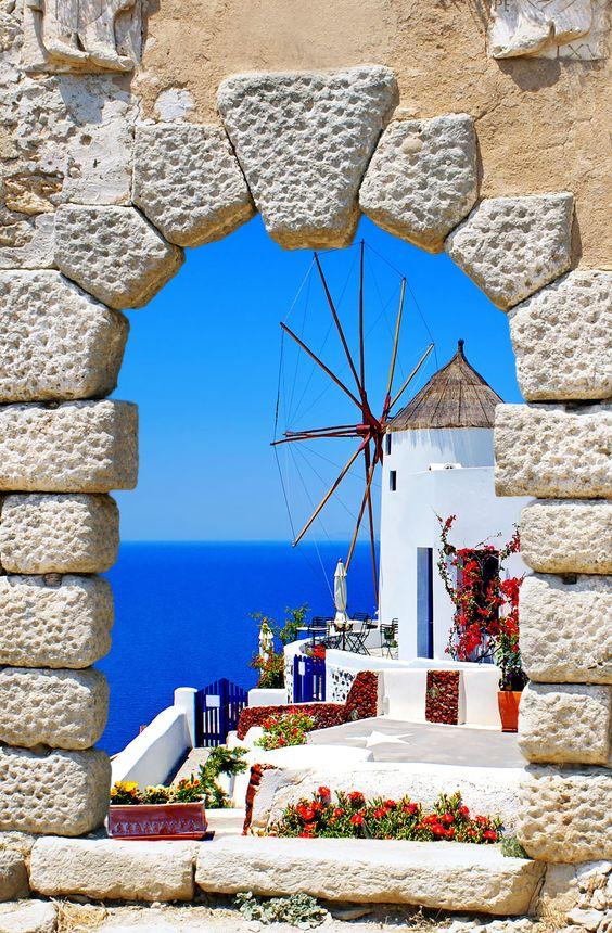 Molino de viento a través de una ventana vieja en la isla de Santorini, Grecia