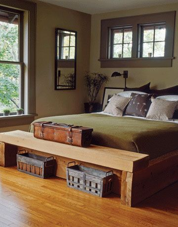 This chunky cedar bed was built with the same material as the room's fireplace mantel. Old zinc Popsicle molds, sometimes pressed into service as vases, reside neatly beneath the footboard-bench, while a leather surveyor's case rests atop it. The walls and linens were kept woodsy yet sleek with khakis and moss greens.