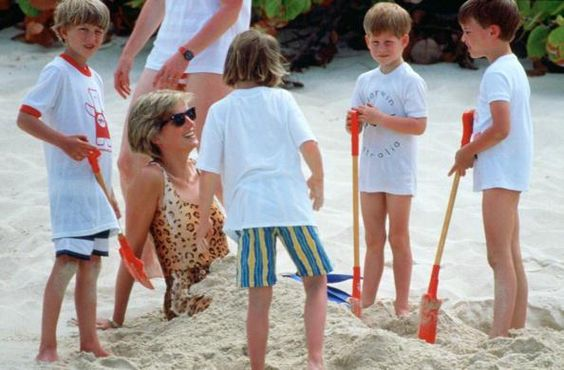 NECKER ISLAND - APRIL 11: Diana, Princess Of Wales, Being Buried In The Sand By Her Sons, Prince William And Prince Harry During A Holiday On Necker Island. Princess Diana Is Wearing A Leopard Sking Swimming Costume. (Photo by Tim Graham/Getty Images) Tim Graham/Getty Images