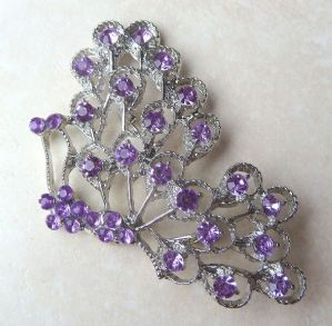 A pretty large purple rhinestone butterfly brooch. The brooch design is of  a butterfly showing its body and one wing, with lovely lilac purple rhinestones set in silver tone metal.  A stunning vintage brooch.