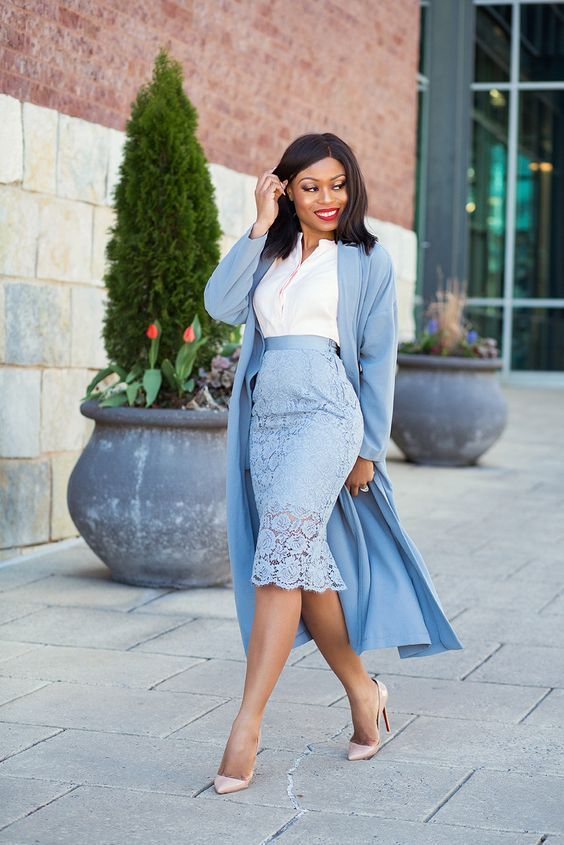 mujer morena elegante en un conjunto azul claro y blusa blanca
