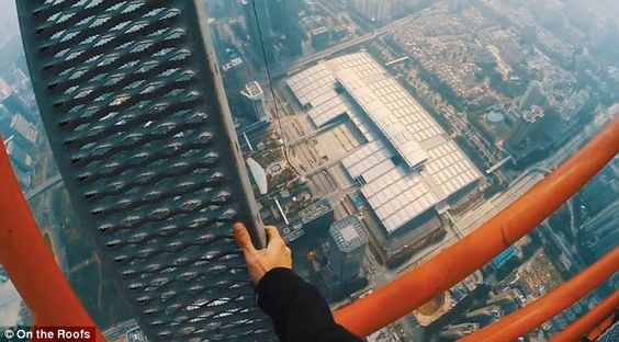 The daredevils free climbed a crane overhanging the very top of the building inShenzhen...