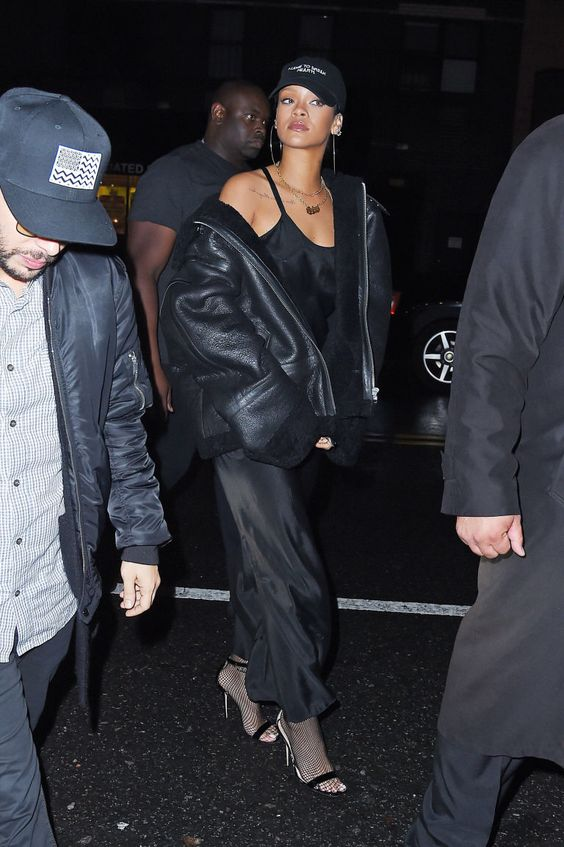 November 19, 2015  After testing out the nightgown-and-baseball-cap look last week, RiRi loved it so much she decided to do it again. Stepping out in NYC to attend her rumored new beau Travis Scott's concert, the singer exuded effortless sex appeal in a black slip dress and leather jacket paired with Manolo Blahnik sandals and sporty headgear.