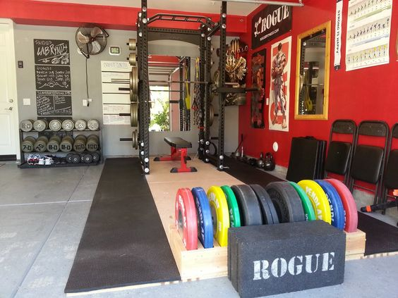Bright and colorful free weights combined with heavy dumbbells and rogue power rack for strength training More