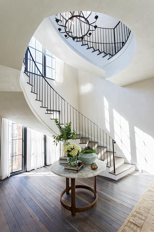 A Round Marble Top Foyer Table Sits On A Wood Floor In Front Of A Curved White Staircas In 2020 Interior Architecture Design House Interior Decor Interior
