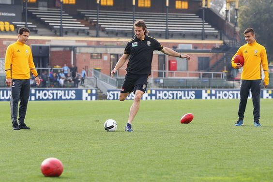 Ivan Maric of the Tigers kicks a soccer ball between Hernanes (L) and Paulo Dybala of Juventus during a Richmond Tigers AFL and Juventus FC media opportunity at Punt Road Oval on July 20, 2016 in Melbourne, Australia.