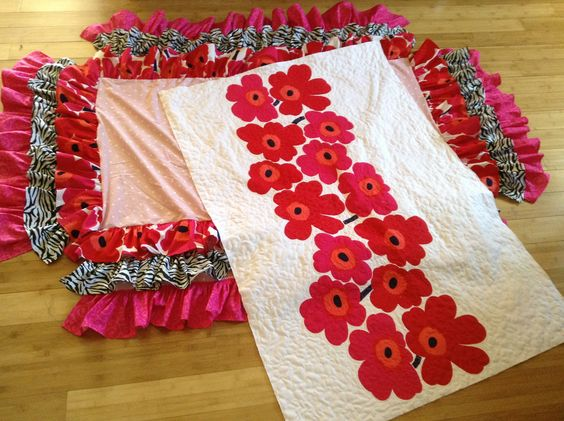 Marimekko crib skirt & modern quilt I made for soon to be granddaughter.  Used a Marimekko sheet and appliqued a band of the flowers on a kona white background then freemotion quilted it.  Easy way to make a bold modern quilt.  The back is soft cuddle fabric.