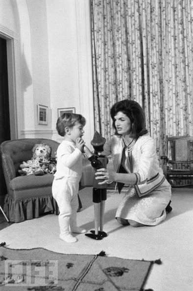 """November 1962: The first lady holds up a wooden toy for her son to inspect. He became known to the public as """"John-John,"""" after a reporter misheard his father calling after him (twice in rapid succession), but his family never used the nickname.: Camelot Kennedys, Jackie Kennedy Onassis, Bouvier Kennedy, Rag Doll, Jfk Jackie, John Kennedy Jr, White House"""