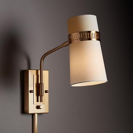 A plug in wall lamp in a warm antique brass finish with a beige linen. A plug in wall lamp in a warm antique brass finish with a beige