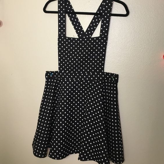 Polkadot Black/White Overall Dress This is an adorable black Polkadot dress from Forever 21. It has a crisscross back with UNADJUSTABLE straps. The straps are buttoned on the back-waist. Only worn once and looks brand new! Last image shows the button where you put the strap. Let me know if you have any questions :) Forever 21 Dresses