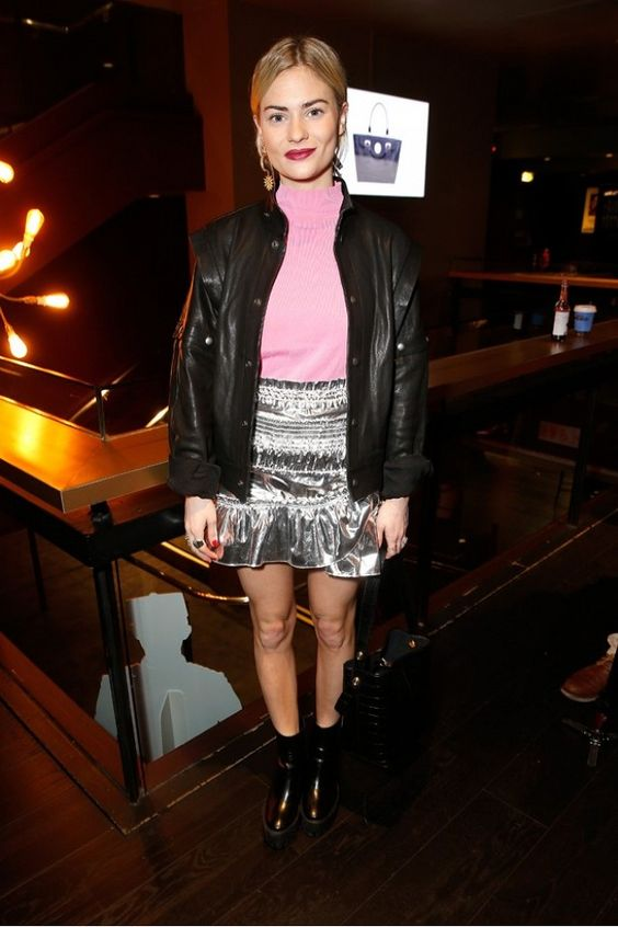 Pandora Sykes wears a pink sweater, leather jacket, metallic miniskirt, and ankle boots