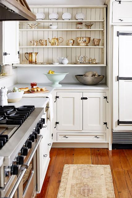 "Gorgeous open shelving with white beadboard and collected English silver and lacework china in this modern farmhouse kitchen. Designer Nicole Fisher created this ""residential retail"" show house and family home for One King Lane president Debbie Propst. #farmhousekitchen #whitecabinets #beadboard #openshelves"