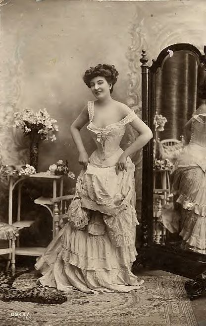 underpinnings.  I think she has just unfastened her bodice.  Corset (no cover) tied at back.  Petticoat (or drawers, i guess) must be held low in front by the corset hook.  Chemise under the corset.