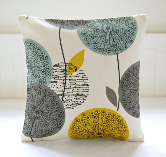 This 16 inch decorative pillow cover has teal, grey and mustard yellow dandelion flower heads and leaves on a soft white / cream background. This