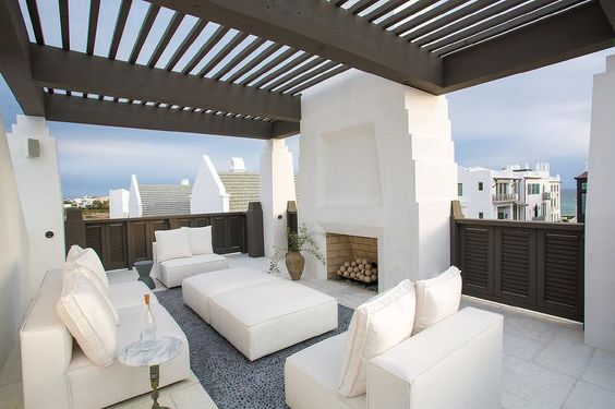 White Mediterranean style deck features cream armless accent chairs paired with matching ottomans doubling as coffee tables placed atop a gray river rock tiled floor facing a white stucco outdoor fireplace shaded by a taupe pergola.