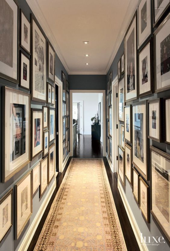 Designer Neal Beckstedt rummaged through cartons of family photos in the attic in order to create a statement-making memory wall in the hallway.: