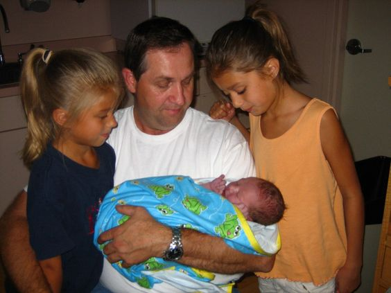 Grandpa Dwight holding his new grandson, Eli's big sisters looking on.