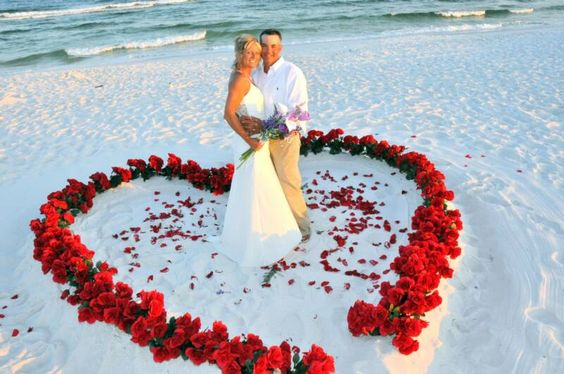 love the idea of making a heart in the sand and filling it with flowers for a beach wedding
