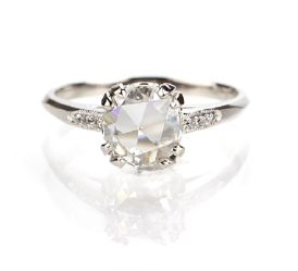 www.antiqueengagementrings.com Replica 1930s Engagement Ring, US $4,525 / Stock Number: 3104-14  Center round Rose Cut diamond weighs 0.95 cts and has been assessed by the UGL appraisal service as J color and SI1 clarity . This beautiful diamond is set with split claw prongs in an elegant and slender platinum ring with six round diamonds bead-set with millegrained edges. This ring is a replica of an original circa 1930's antique engagement ring.