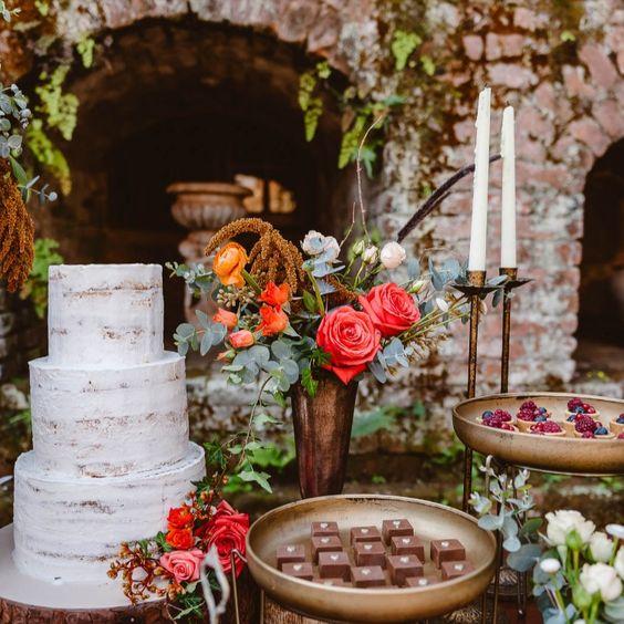 Uma Mesa de bolo e doces perfeita para seu Destination Wedding na Europa com tons terrosos e composição de flores e frutas